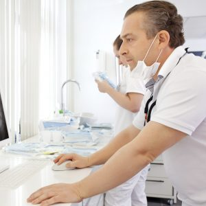 Dentist looking at an xray on a computer - dental cyber liability insurance